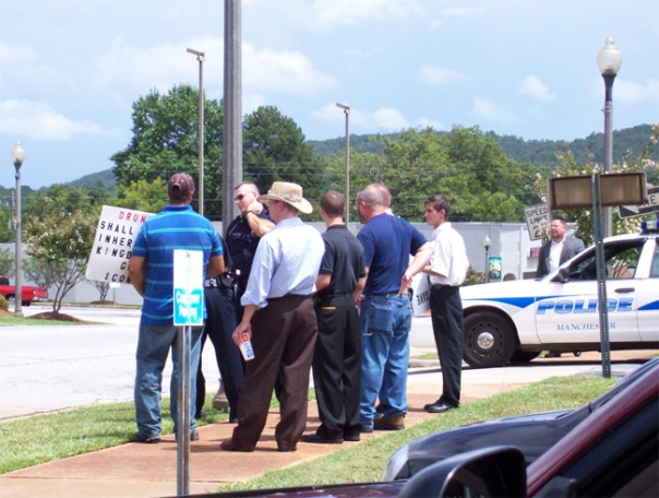 Police confront  Pettigrew's group while they hold signs