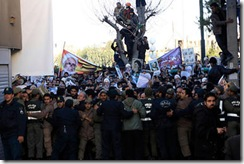 Iranian police officers, foreground, prevent mourners from approaching the house of the Grand Ayatollah Hossein Ali Montazeri, the spiritual father of Iran's reform movement, prior to his funeral ceremony, in the city of Qom, Monday.